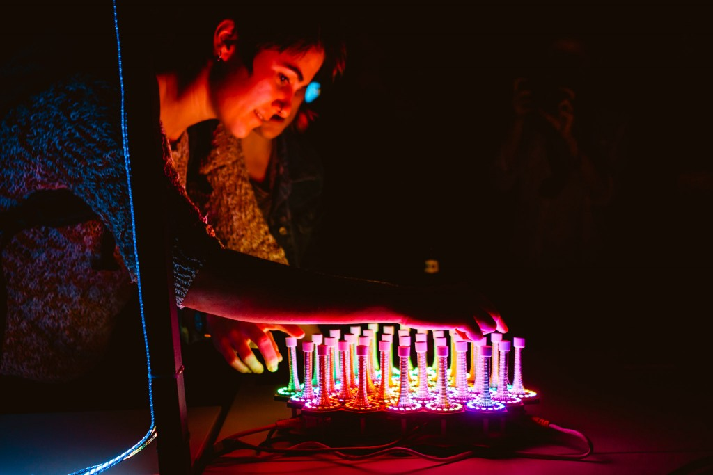 Two people playing a brightly lit collection of LED lit springs.